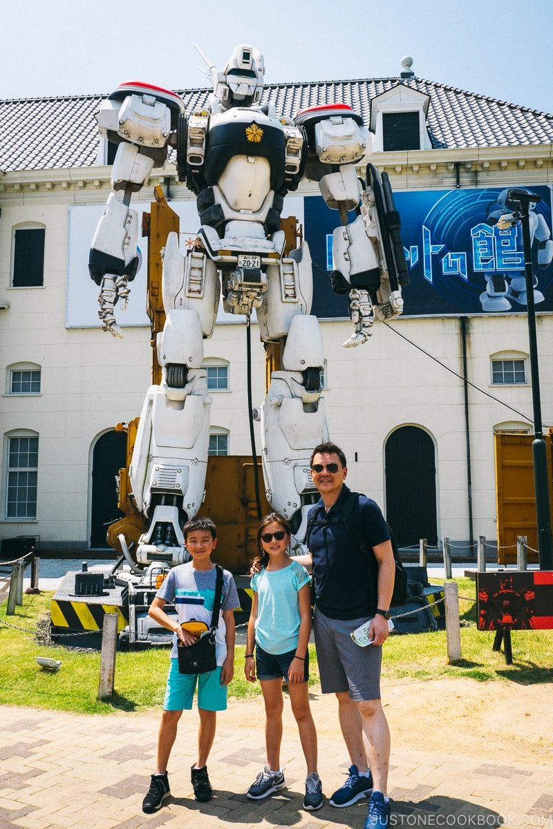 a man and two children standing in front of a robot