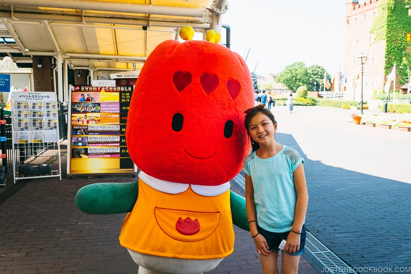 girl standing next to Huis Ten Bosch mascot