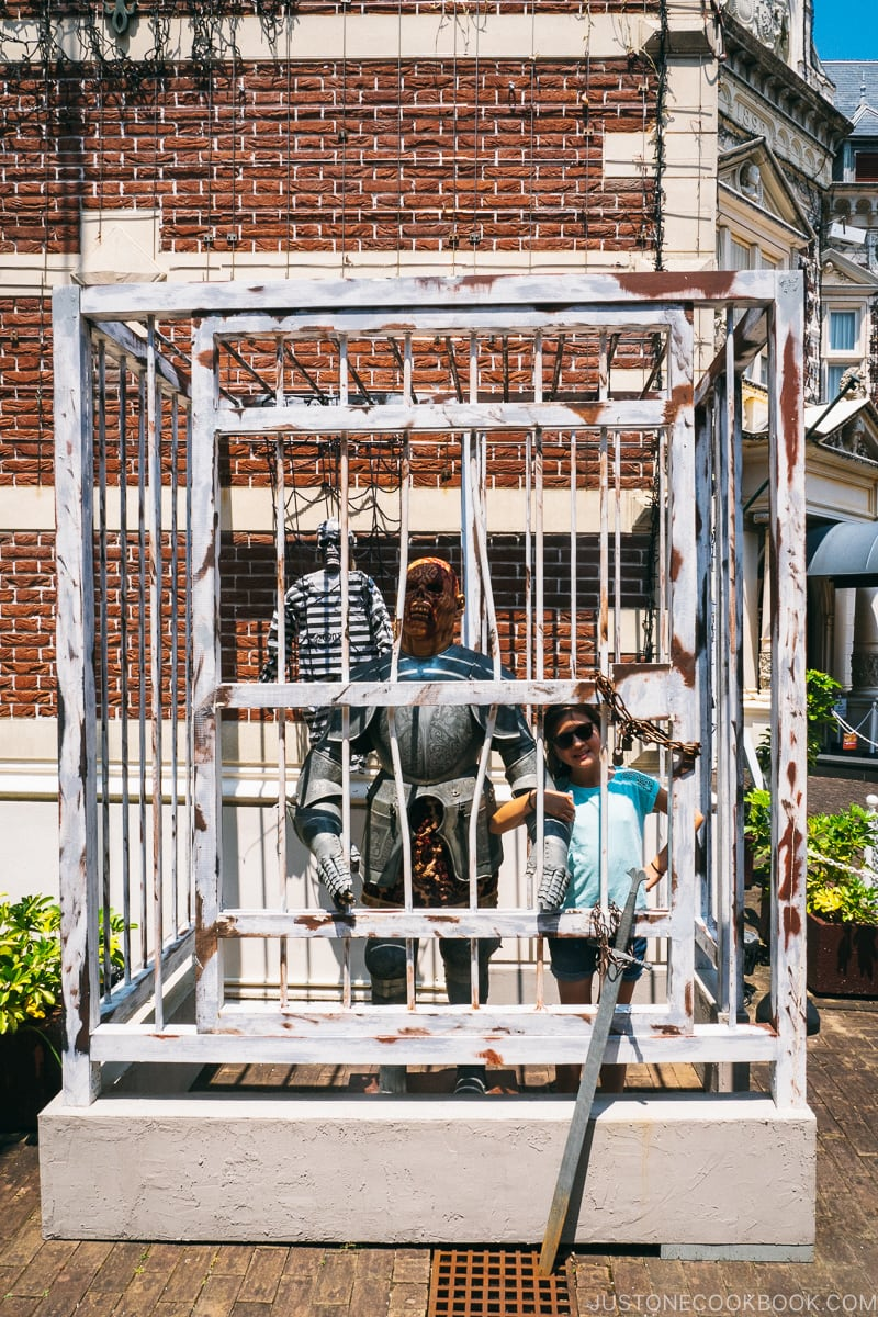 girl with model of a scary creature behind bars
