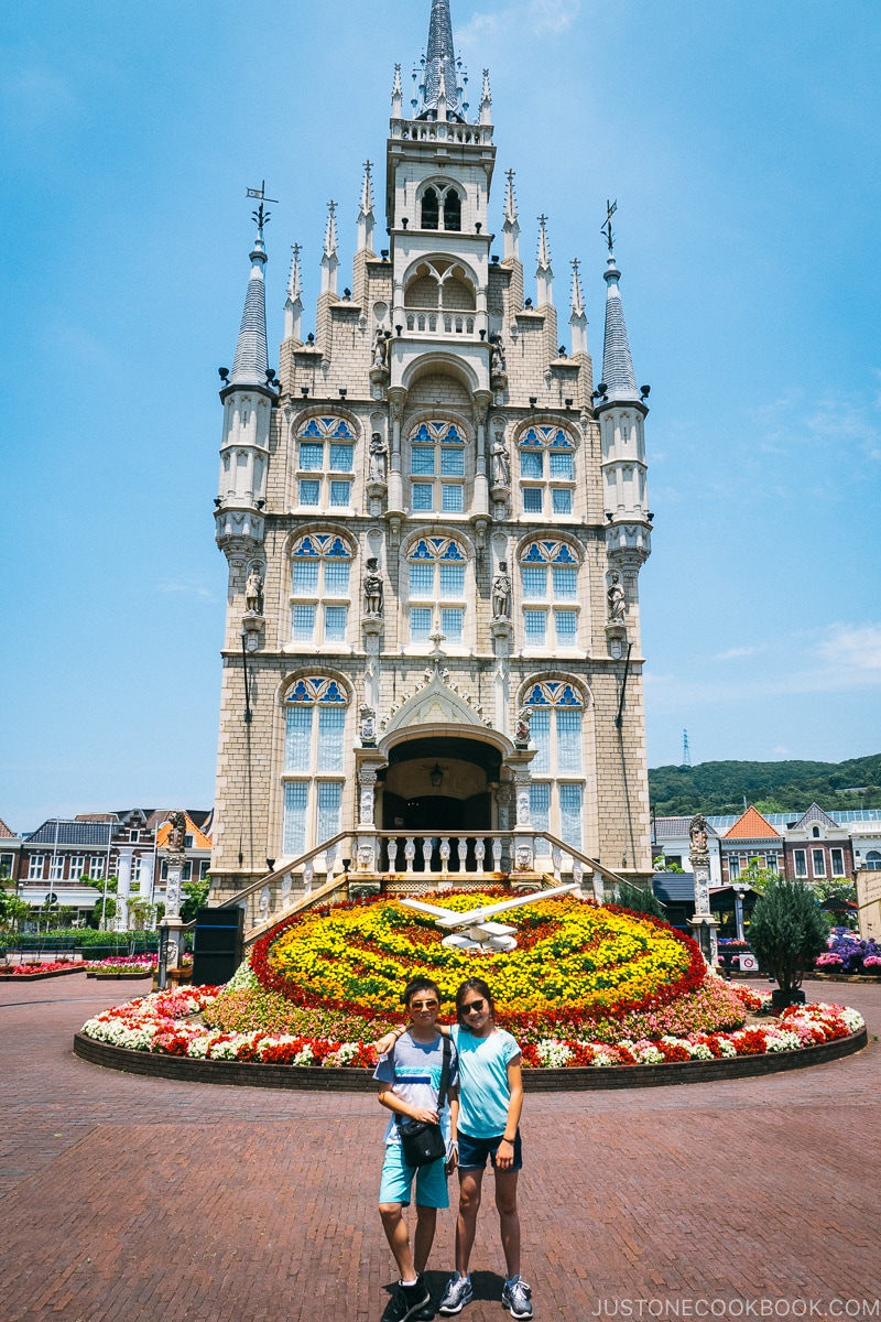two children in front of a flower bed clock and three story castle
