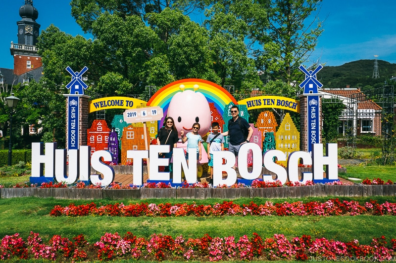 a family standing behind Huis Ten Bosch sign in a flowerbed