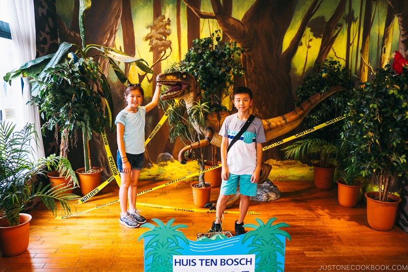 girl and boy in front of dinosaur sculpture and plants