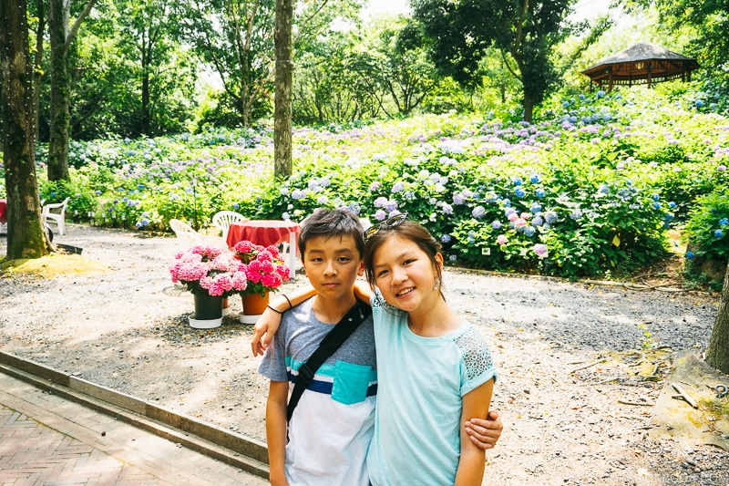 girl and boy in front of hydrangea flowers