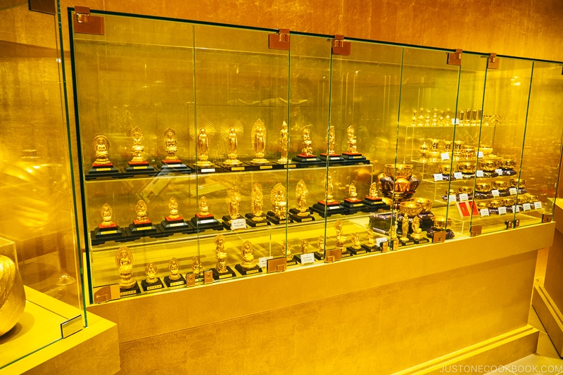 gold buddha statues inside a glass case
