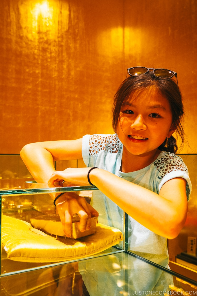 girl trying to pick up a gold bar