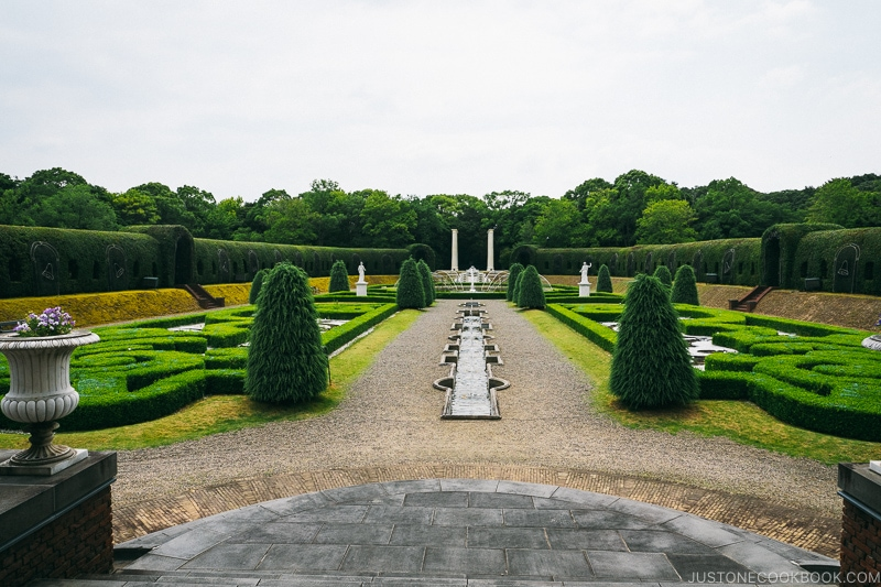 european style garden with hedges and trees and rock walking path