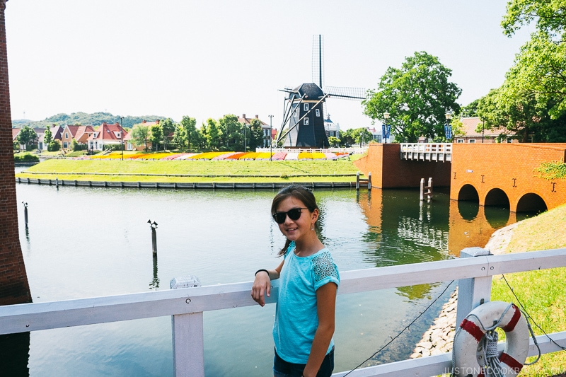 girl on a bridge in front of a body of water and windmill in the background