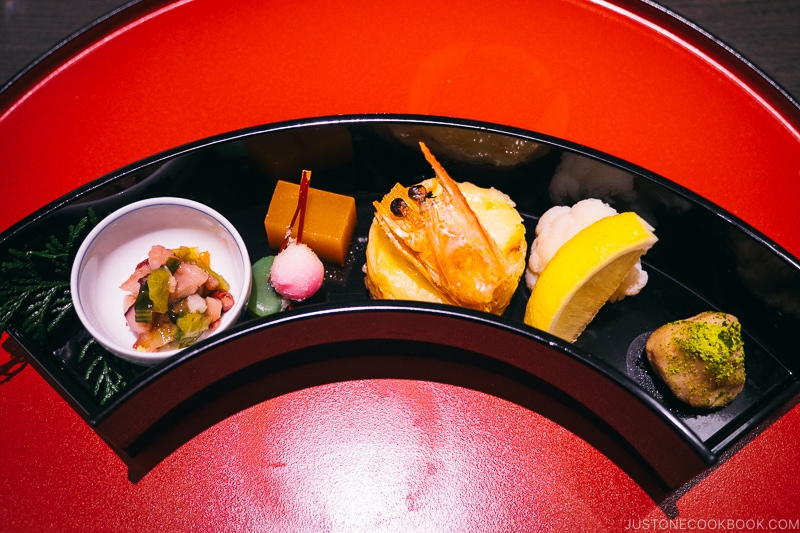 assorted appetizer in a black moon shape bowl