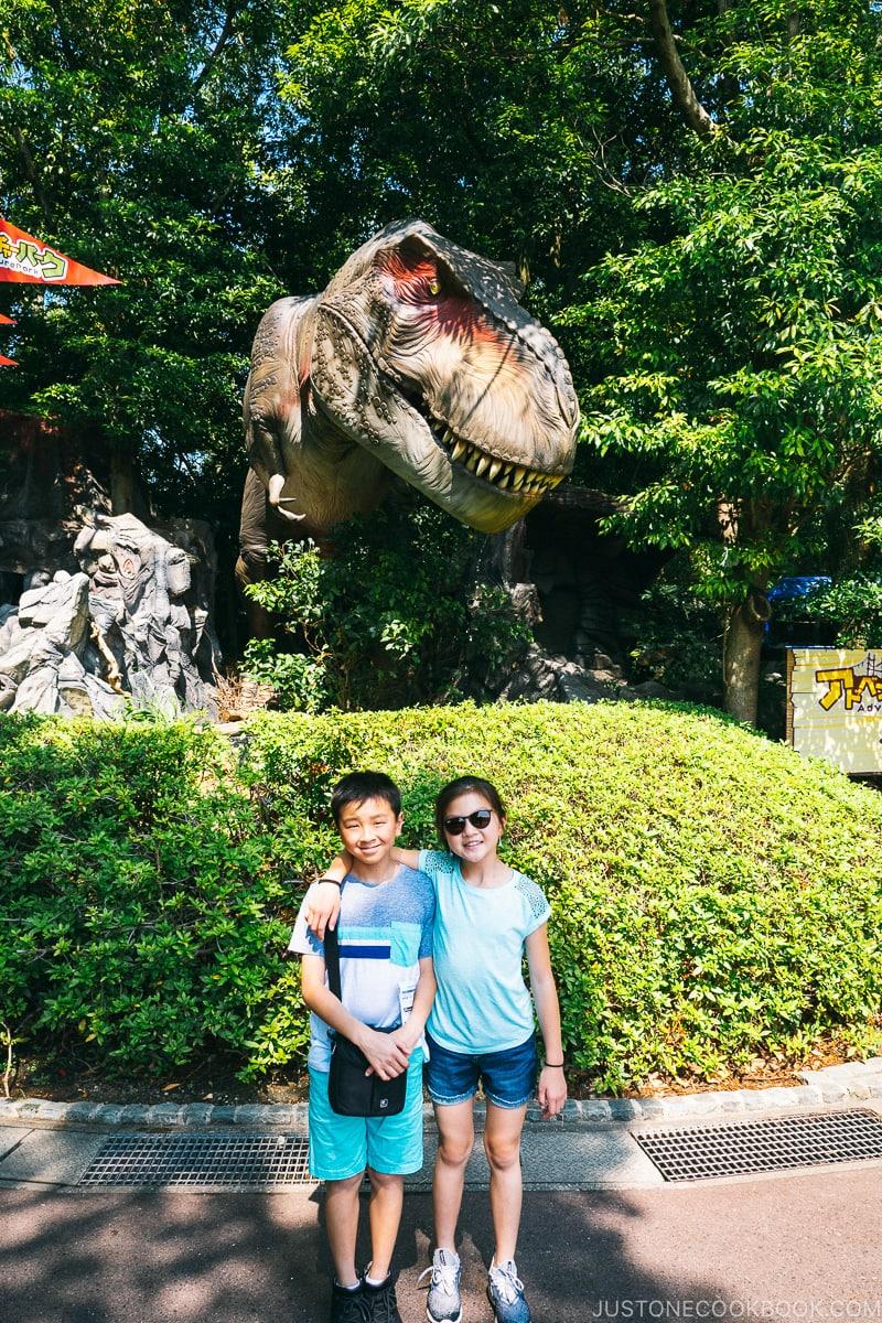 two children in front of mechanical dinosaur inside trees