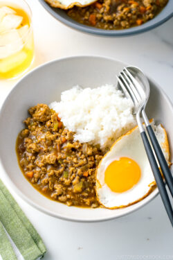 A bowl containing Keema Curry, steamed rice, and a fried egg.