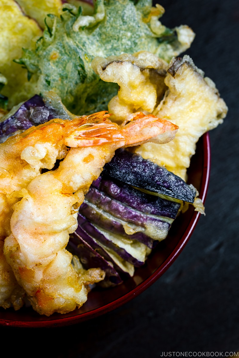 Assorted tempura served on a bed of steamed rice in a red lacquered bowl.