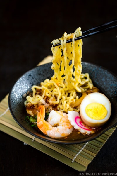 A black bowl of Tsukemen dipping sauce and a white bowl containing noodles with toppings.