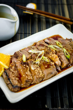 A white plate containing beef teriyaki sprinkled with sesame seeds and scallion.