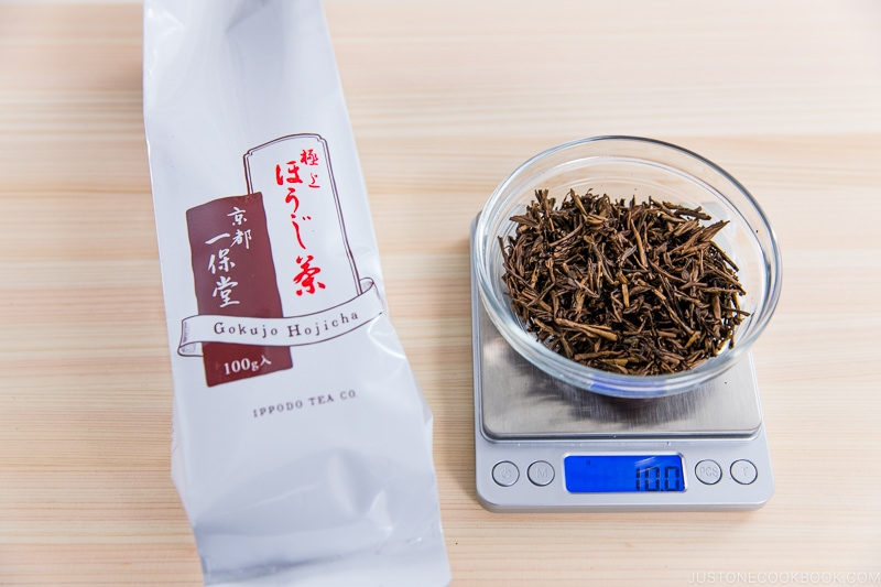 10 grams of hojicha on a scale next to a package on cutting board