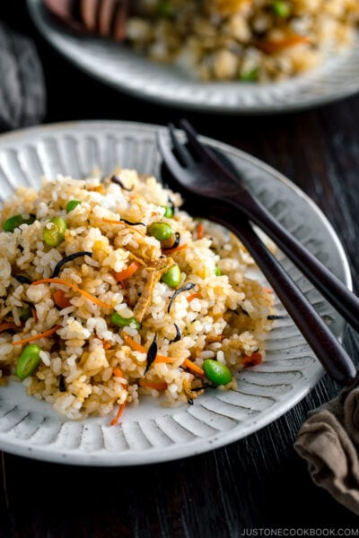 Japanese Fried Rice with Edamame, Tofu and Hijiki Seaweed on a white plate served with wooden utensils.
