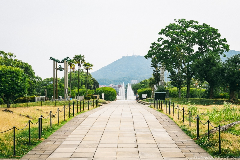 a walkway with fountain at the end