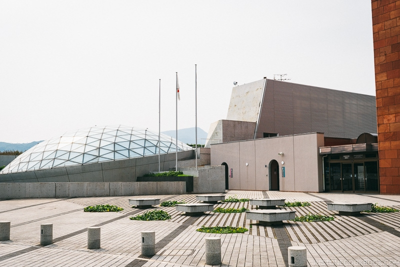 a concrete plaza with glass dome of Nagasaki Atomic Bomb Museum in the back