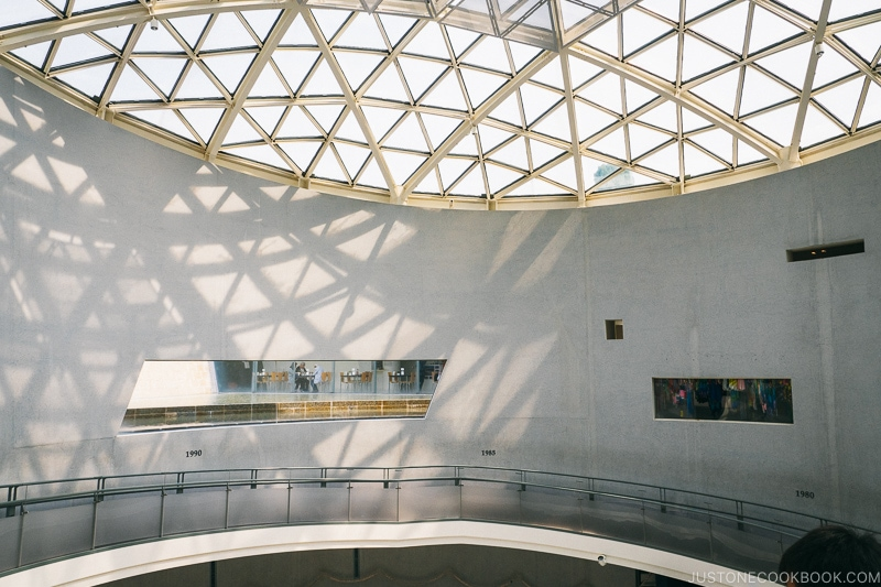 inside Nagasaki Atomic Bomb Museum building with glass dome ceiling and floating walkway along the wall