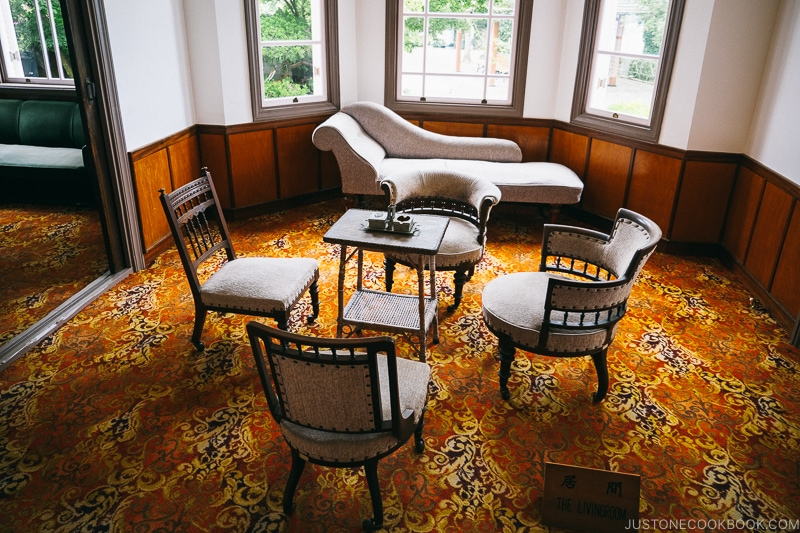 a carpeted room with a lounger and small table with four chairs around it