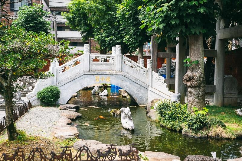 a white bridge over a small pond