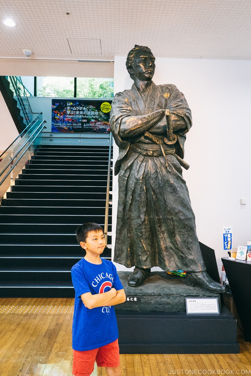 boy in front of a Sakamoto Ryōma statue