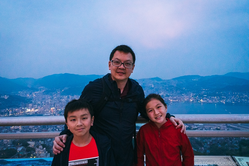 man with two children with city of Nagasaki in the background