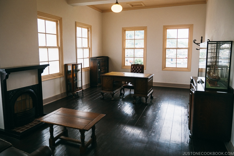 room with a fireplace, antique coffee table, office desk and chair with dark wooden floor