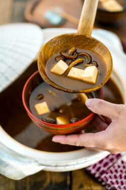 Nameko Miso Soup being served fro a donabe to a wooden bowl.