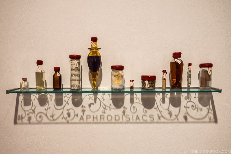 Aphrodisiacs by John Hatfield with bottles on a glass shelf and casting shadows below