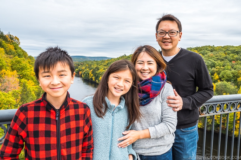 family standing on a bridge above a river with trees in the background
