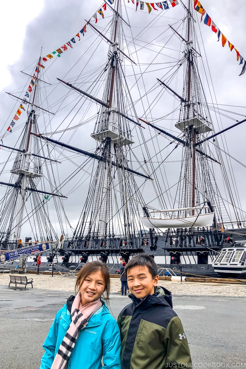two children standing in front of USS Constitution