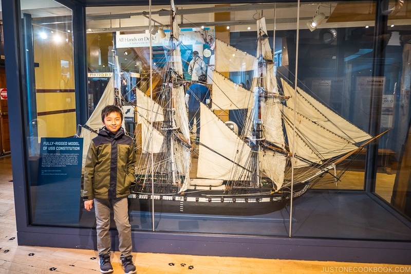 boy standing in front of a fully-rigged model of USS Constitution