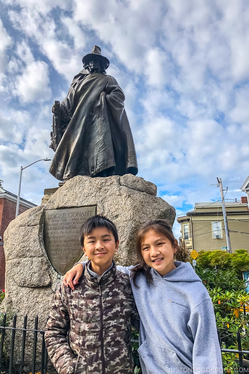 two children in front of Roger Conant statue