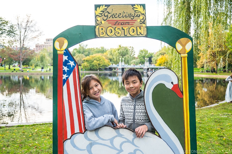 two children standing in a Greetings from Boston frame