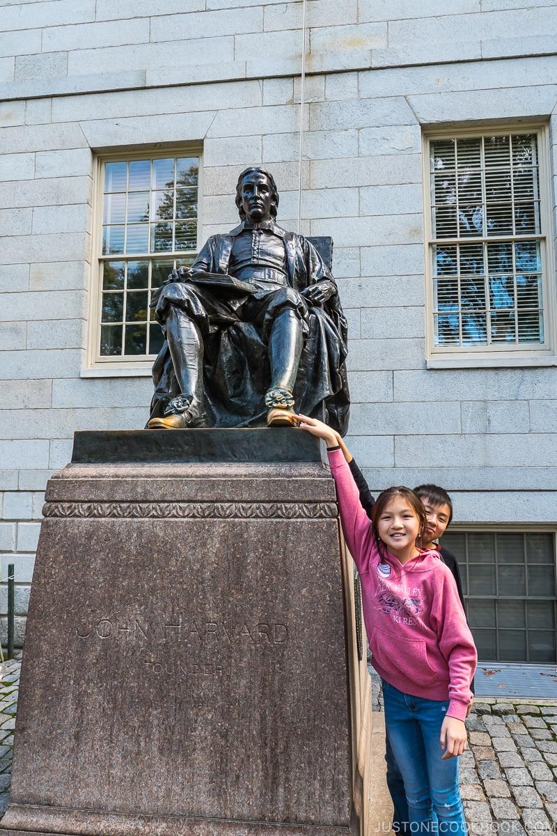 two children touching the toe of John Harvard statue