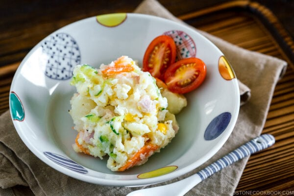 A ceramic bowl containing Japanese potato salad and cherry tomatoes.