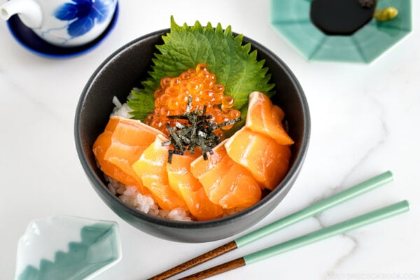 A black bowl containing a bed of rice topped with sashimi grade salmon, ikura, and shredded nori.