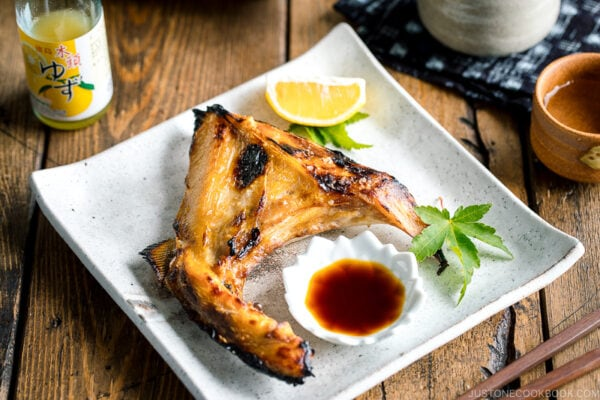 A white Japanese ceramic plate containing Hamachi Kama (Grilled Yellowtail Collar) along with a wedge of lemon and yuzu-soy dipping sauce.