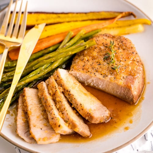A white plate containing honey garlic pork chops, roasted carrot, and asparagus.