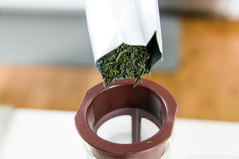 green tea leaves being pour into a cold brew pitcher