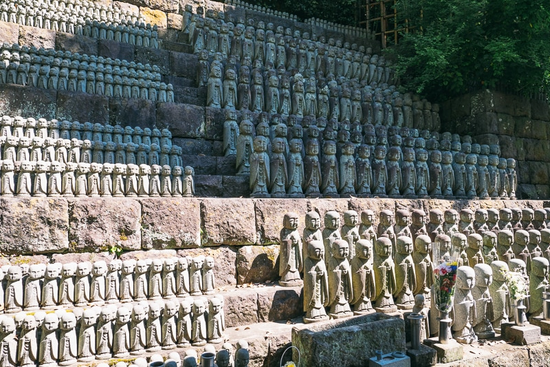 hundreds of stone jizo statues lined up on a hill