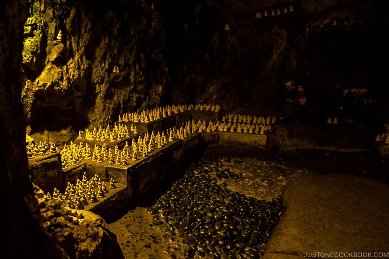 small jizo statues lined up inside a cave