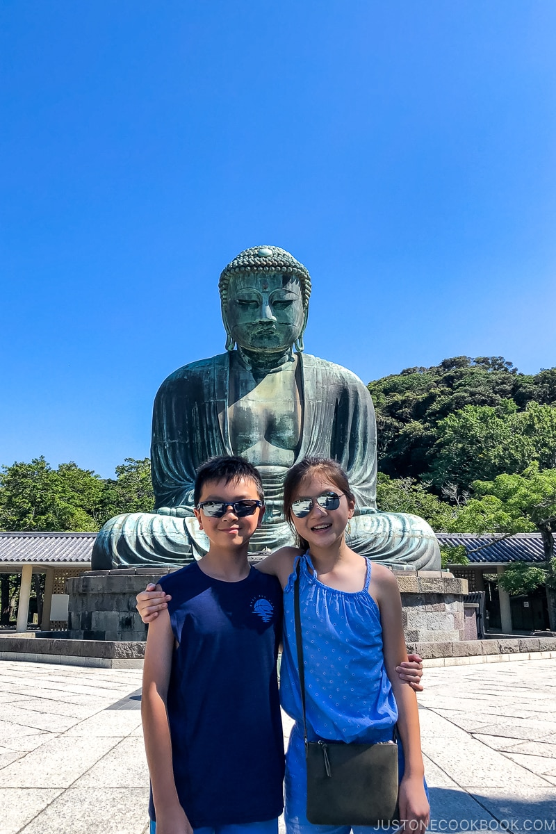 two children standing in front of a giant Buddha statue