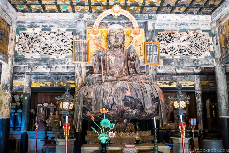 an old statue of deity sitting on lotus