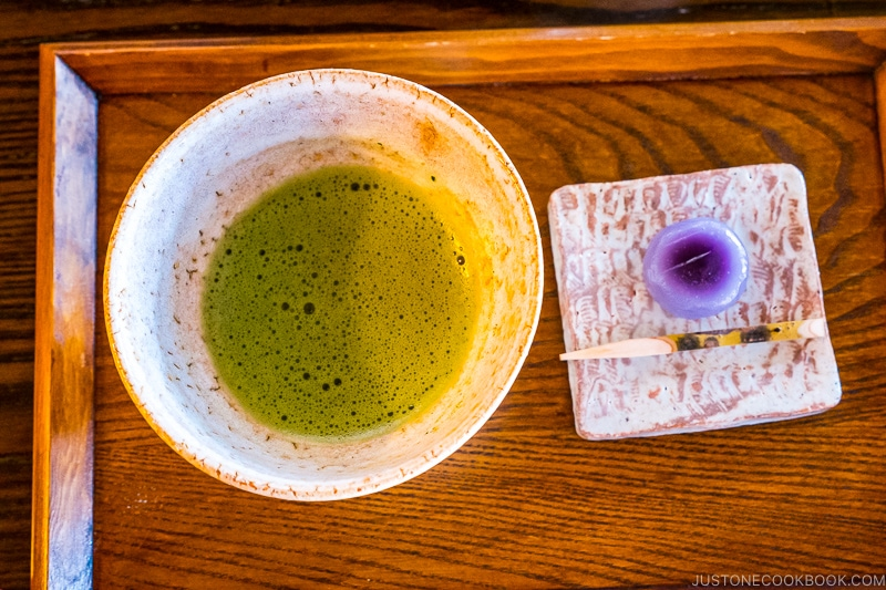 a wooden tray with matcha green tea on in a bowl on the left and sweets on the right