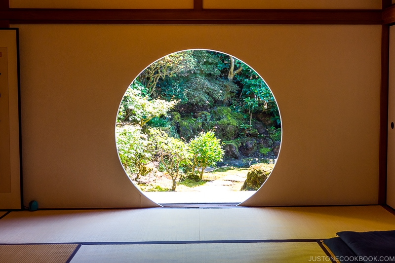 a Japanese room with tatami and a circle cut into a wall looking into a garden