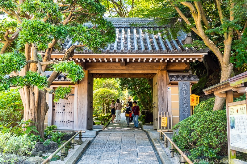 a wooden gate with tiled roof over a stone path