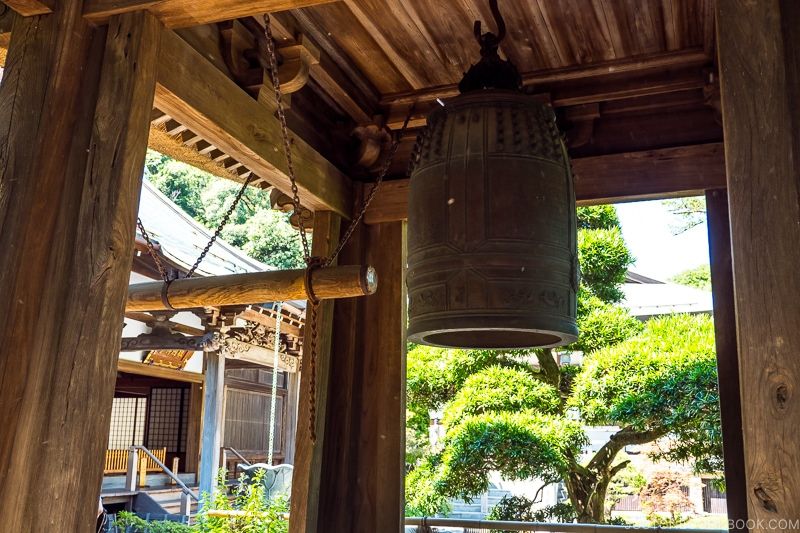 a temple bell hanging in a wooden structure