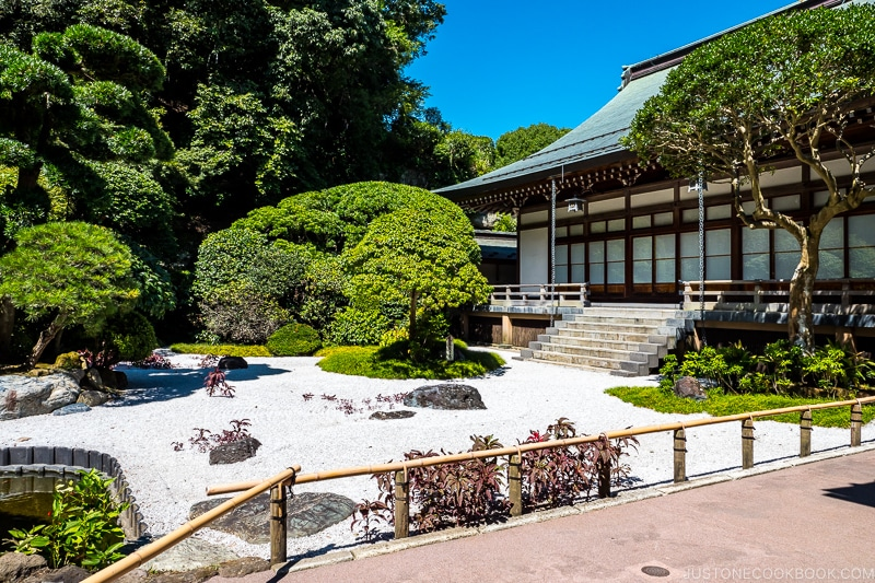 a rock garden next to a temple with trees in the back