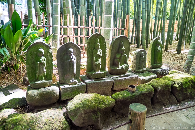 stone statue of deities on stone pedestal in front of bamboo garden